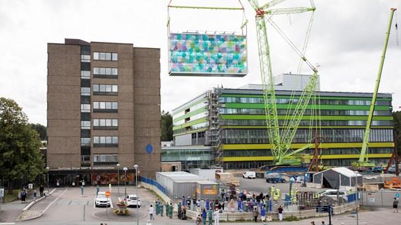 Förbindelsegången mellan det nya och gamla barnsjukhuset lyfts på plats av en kran. Många människor tittar på.